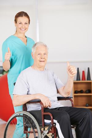 geriatric nurse: Old senior patient in wheelchair and geriatric nurse holding thumbs up