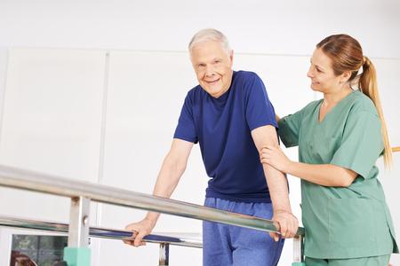 Oude man in de fysiotherapie op de loopband met horizontale balken en fysiotherapeut Stockfoto