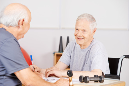 eldercare: Old man in nursing home with crossword puzzle for memory training Stock Photo
