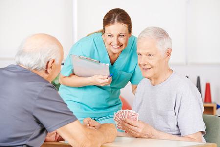 nursing allowance: Smiling geriatric nurse watching twi old men playying cards in a nursing home