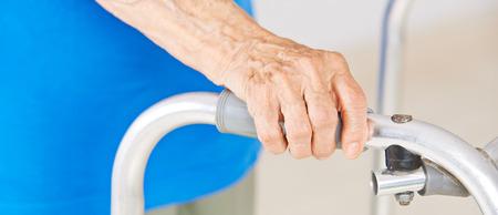 nursing allowance: Hands of senior woman using a walker for support Stock Photo