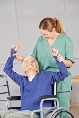 terapia ocupacional: Mujer de edad avanzada haciendo fisioterapia en casa de reposo con la enfermera geriátrica
