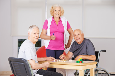 nursing allowance: Three happy senior citizens playing Bingo together in a nursing home Stock Photo