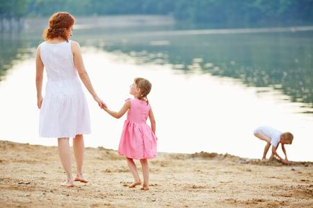 persona caminando: Madre que juega con dos niños en una playa en verano