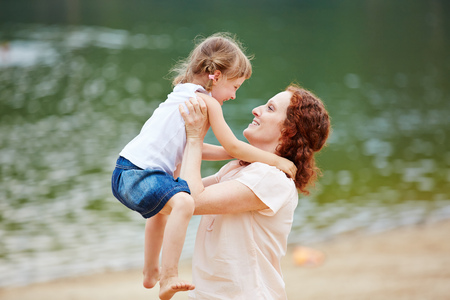 carry on: Happy mother lifting smiling daughter on a beach