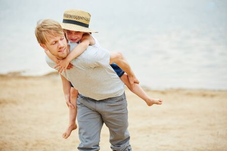 carrying girl: Man carrying girl piggyback on his back on a beach in summer Stock Photo
