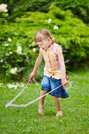 saltar la cuerda: Ni�a jugando con saltar la cuerda en el jard�n en verano Foto de archivo