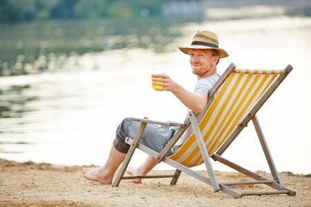 homme détendu boire de la bière dans la chaise longue en été