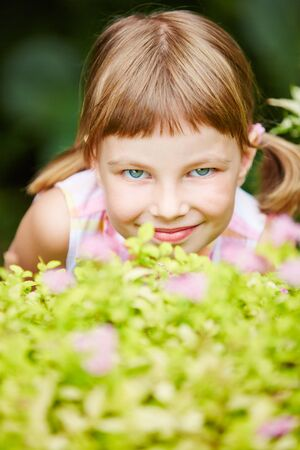 hide and seek: Smiling girl playing hide and seek in garden and hiding behind a bush