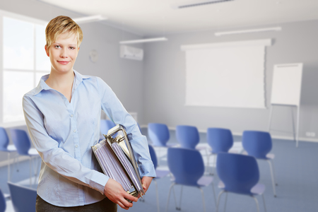 job training: Smiling woman standing with many files in a seminar room (3D Rendering) Stock Photo
