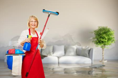 Señora de la limpieza en la habitación con el daño del agua después de fugas de tuberías Foto de archivo