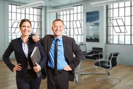 Two happy business people standing in a modern loft office (3D Rendering) 写真素材