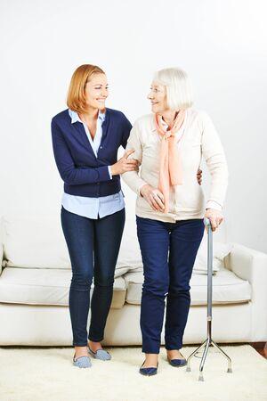 Caregiver du service de soins infirmiers en aidant femme âgée avec la canne à la maison