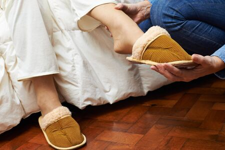 get help: Hands of a caregiver helping feet of senior woman putting on slippers at home Stock Photo