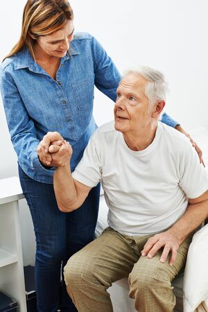 geriatric care: Daughter helping old senior man getting up from bed