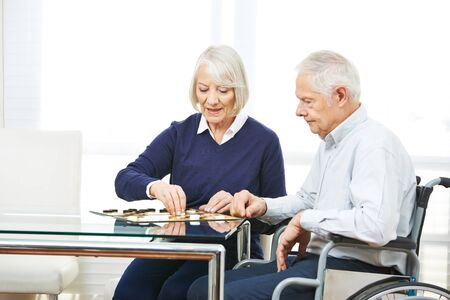 social work aged care: Happy senior couple playing checkers in nursing home