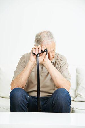 cane sofa: Sad senior man with cane sitting on a sofa Stock Photo