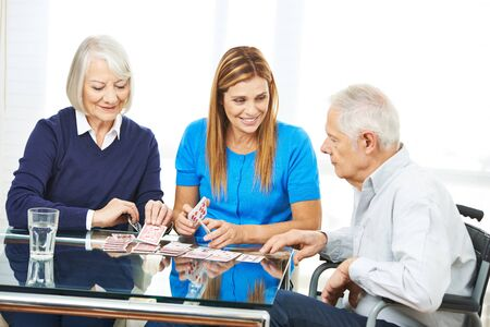 social work aged care: Happy senior couple playing cards with woman at table Stock Photo