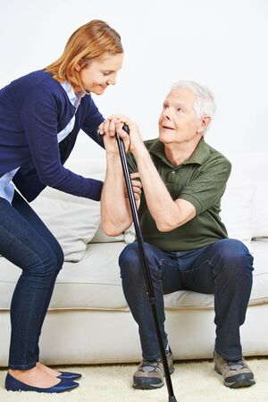 get help: Woman helping senior man with cane getting up from sofa at home