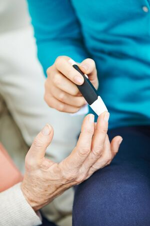 blood glucose: Blood glucose monitoring for old woman on her finger
