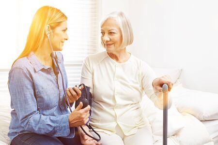 eldercare: Woman doing blood pressure monitoring in nursing home for senior woman