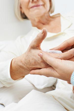 eldercare: Hands washing bedridden senior woman at home