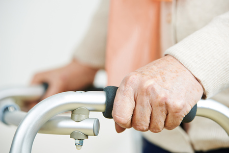 nursing allowance: Hands of an old woman holding on to a walker