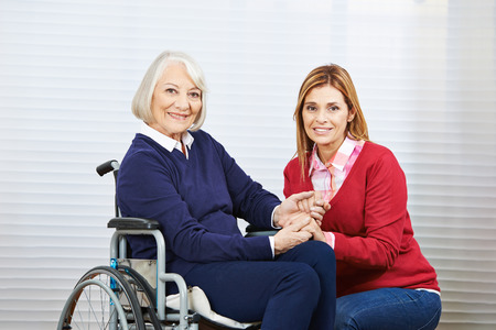 social work aged care: Young and old woman holdind hands together in a nursing home