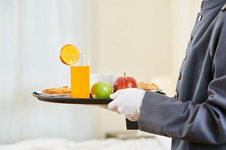 El servicio de habitación que trae el desayuno saludable con jugo de naranja y frutas