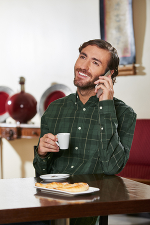 Man in hotel drinking espresso and making a phone call with his smartphone Stock Photo