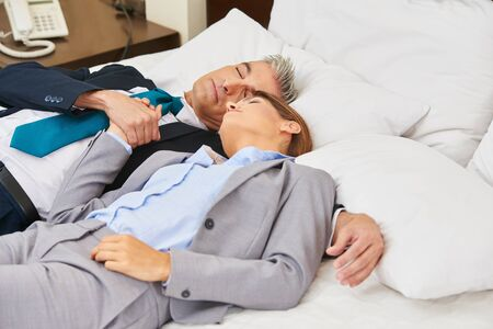 couple relaxing: Business couple sleeping on bed in a hotel room Stock Photo