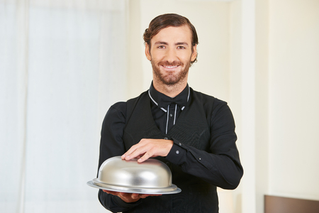 hospitality staff: Smiling hotel clerk serving food with cloche on a tablet