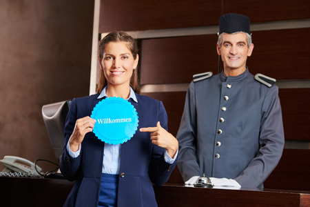 hospitality staff: Woman pointing to German sign saying Willkommen (welcome) at the reception Stock Photo