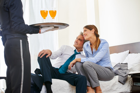 hotel room: Hotel page serving drinks to business couple in a hotel room