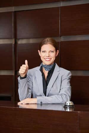 hospitality staff: Smiling female hotel receptionist holding her thumbs up Stock Photo