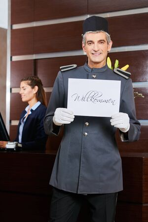 willkommen: Smiling hotel concierge holding sign saying in German Willkommen (welcome)