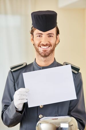 hospitality staff: Smiling hotel page with white empty sign and food cloche in hotel room