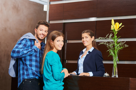 hospitality staff: Young couple with receptionist during hotel check-in at the reception