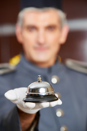 hospitality staff: Concierge holding hotel bell on his hand with gloves Stock Photo