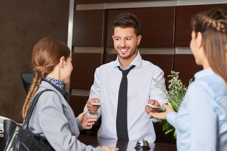 hospitality staff: Hotel receptionist giving out key cards to guests Stock Photo