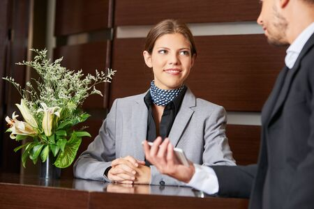 hotel receptionist: Friendly hotel receptionist and business guest at check-in