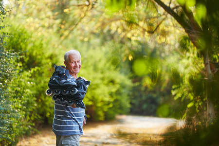inline: Active senior with inline skates in the nature Stock Photo
