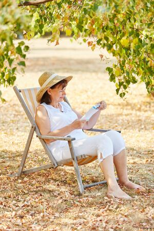 deck chair: Senior woman sitting on a deck chair relaxing and reading