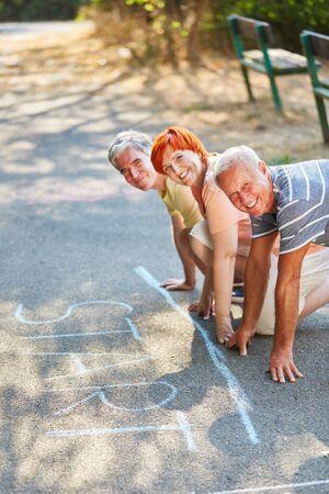 suspenso: Personas felices de la tercera edad listos para comenzar la carrera en el parque en verano