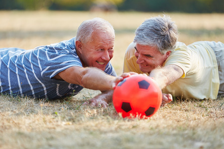 happy seniors: Two seniors reaching ball during soccer match in the park in summer