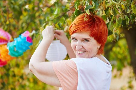 Senior woman decorating for a party in the park Stock Photo