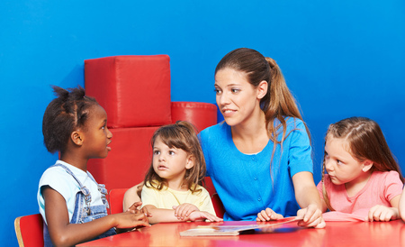 Children talking during language promotion in kindergarten with speech therapist Stock Photo