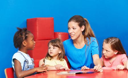 Hablar de los niños durante la promoción de la lengua en el jardín de infancia con terapeuta del habla Foto de archivo