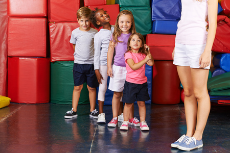 preschool children: Children standing in a row in gym of preschool with PE teacher