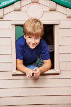 looking through window: Smiling boy looking through window in a playhouse in kindergarten